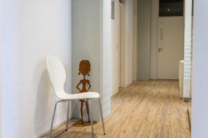 Gang mit Holzboden, Figur und weißem Stuhl