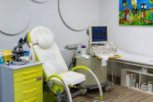 Behandlungsraum mit Sessel und Regal hellgrün und Computer