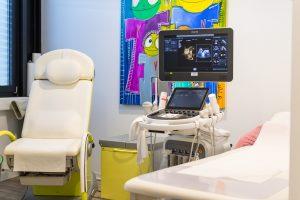Behandlungsraum mit buntem Bild und Stuhl und Liege