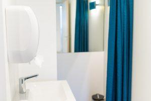 Umkleide mit Waschbecken und blauem Vorhang