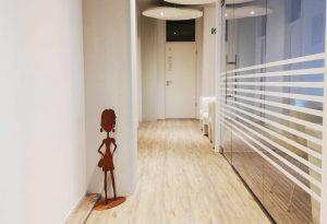 Blick in den Gang der Praxis mit Boden Figur, Holzboden und hellen Wänden
