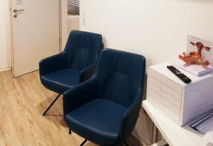 zwei blaue Wartrsessel auf dem Gang vor der Behandlungsräumen